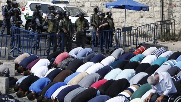 Palestinian Muslim worshippers, under the age of 40 years old, perform the traditional Friday prayers on a street as Israeli police blocks the access to Al-Aqsa Mosque, on October 2, 2015, at Jerusalem's Old City Lion Gate outside the Al-Aqsa mosque compound. AFP PHOTO /AHMAD GHARABLI        (Photo credit should read AHMAD GHARABLI/AFP/Getty Images)